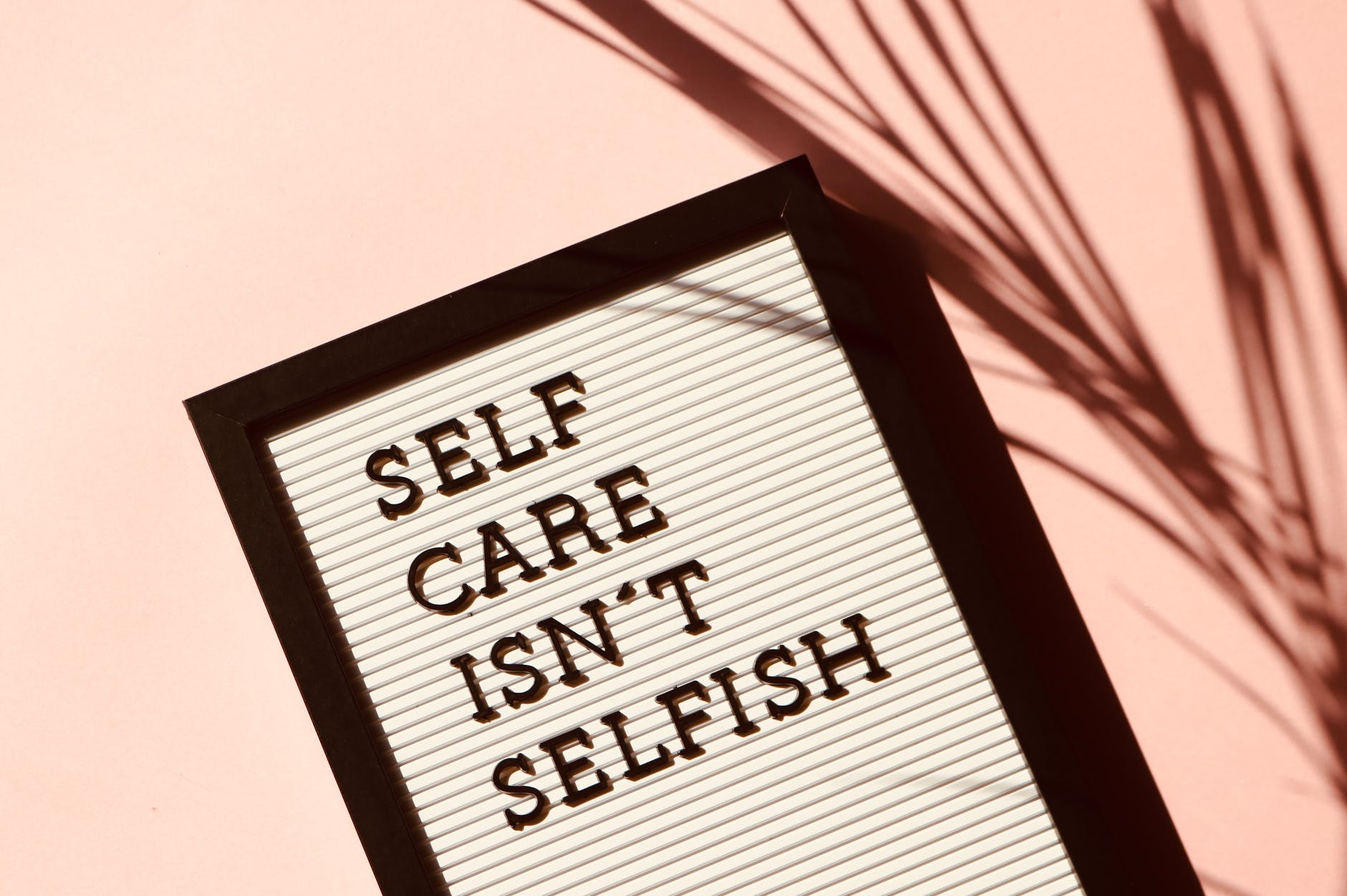 """sign that reads, """"self care isn't selfish"""""""